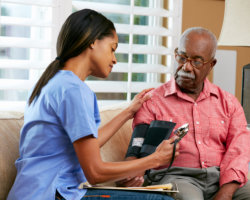 caregiver checking the blood pressure of patient